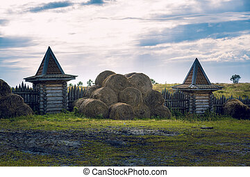 Round bales of hay in a fenced-fence manor house