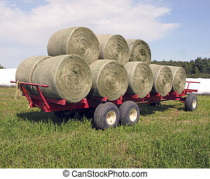 round bales of hay stacked on trailer ready to be wrapped in white plastic for storage