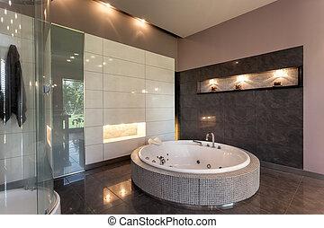 Round bath in a luxury tiled bathroom interior