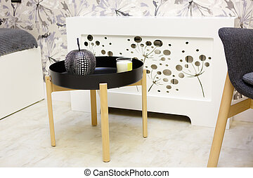 Round black bedside table. On the table are candlesticks and a black apple-shaped vase.