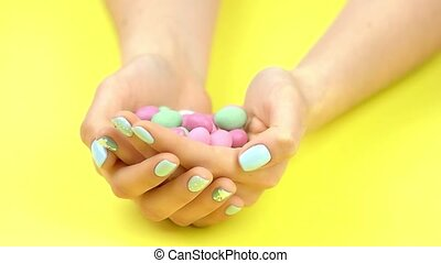 Round candies falling into palms, slow motion. Woman hands...