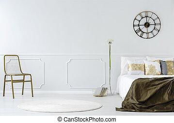 Round clock in bedroom interior