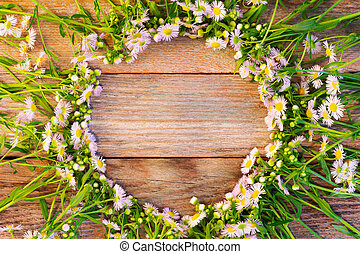 round frame made of chamomile on wooden vintage background with space for text top view. mock up for text, phrases, lettering