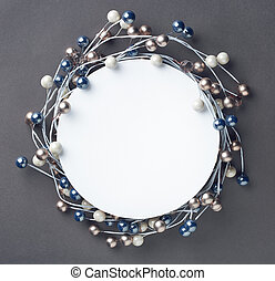 Round frame of Christmas baubles decorations and blank paper card with space for text. Top view. On gray background.