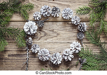 Round frame of white pine cones with fir branches on a old wooden  table. Christmas background. Space for text.