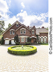 Round garden and paving in front of a big, english style house