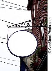 A blank circular hanging sign outside a store font or shop with copyspace for your text or logo. Clipping path is included in the file.