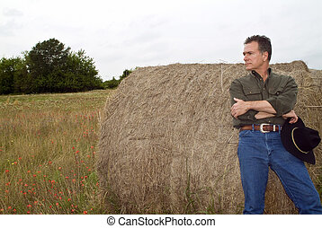 Round Hay Bale - A man resting against a large round bale of...