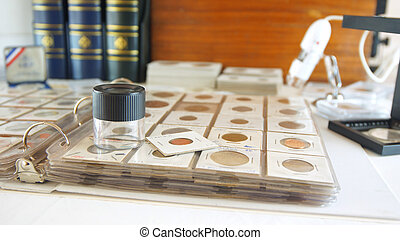 Round magnifying glass on album with coins from different countries - Numismatic scene