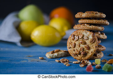Round orange biscuits with colorful candied fruits and a slice of juicy orange lying on a wooden table