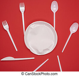 round plate and stack of plastic forks and spoons on red background