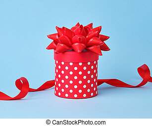 round red cardboard box in white polka dots on top of a bow on a blue background