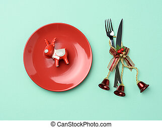 round red ceramic plate, knife and fork on green background, festive table setting
