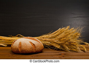 Round rye bread and a sheaf on wooden table, black background, space for text