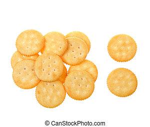 Round salted crackers randomly strewn on white background...