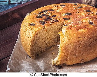 Round-shaped homemade bread with seeds in a cut on a wooden dark tray, closeup shot
