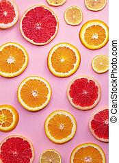 Round slices of grapefruit, orange and lemon on a pink background