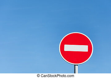 Round stop sign against a blue sky.