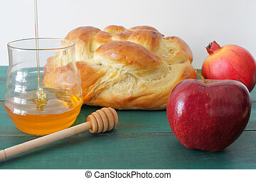 Round sweet challah, honey jar, red apple and pomegranate on...