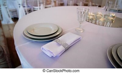 round table with a white tablecloth served plates wine...