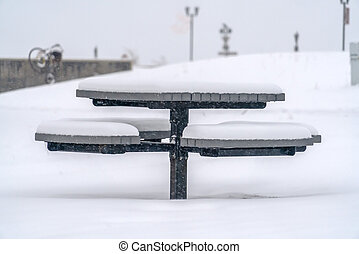 Round table with seats covered with snow in winter