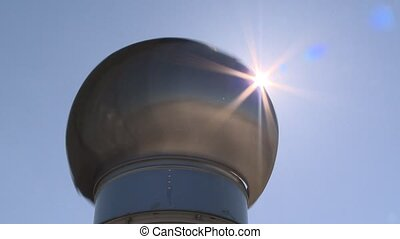 Round ventilator spin and sun rays beams visible on blue sky...