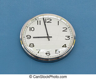 Round wall clock hanging on blue cement wall