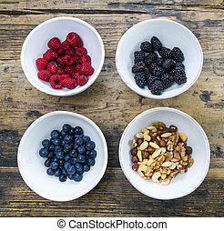 round white ceramic bowls with berries and nuts on a rustic wooden table