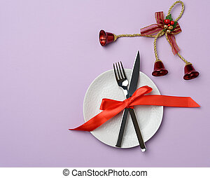 round white ceramic plate, knife and fork on a purple background