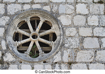 Round window in an old stone wall