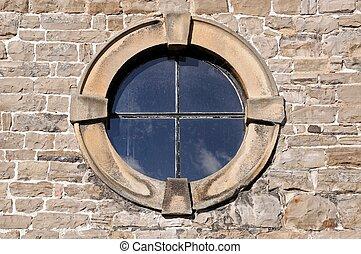 Round window in stone frame.