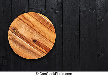 Round wooden serving plate on black wooden table