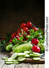 Round zucchini slices and fresh radish, vintage wooden background, selective focus, shallow depth of field