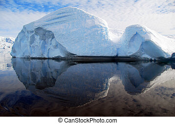 rounded iceberg floating in the ocean, reflected in water