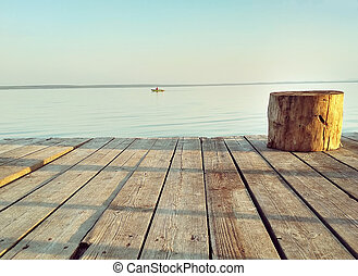 Rounded wooden seat on a sub pier on the background of a calm summer lake at sunset