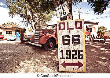 Old rote 66 signs with rusty cars in background