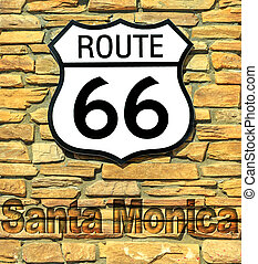 United States historic Route 66 road sign of Santa Monica on a brick wall. American highway from Chicago city of Illinois to Santa Monica town in California.