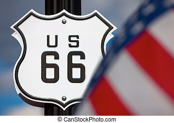 Route 66 sign on side of road with American flag