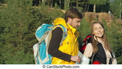 Route Planning - Close up of young backpackers consulting a...