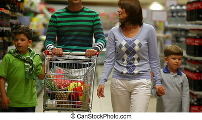 Routine - A family of four walking in the supermarket with a...