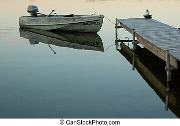 Old row boat with motor tied up to wooden dock in calm water in an inland lake.