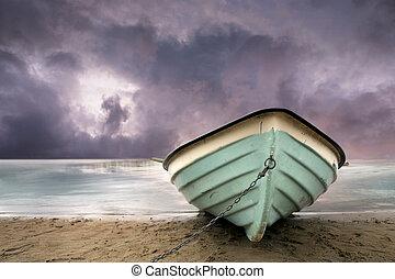 row boat on sandy beach with purple sky