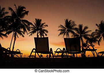 Row deckchairs on beach at sunset, Tanjung Aru, Malaysia