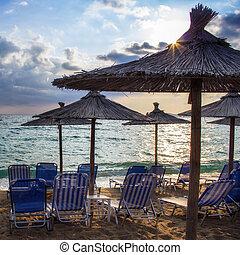 Row deckchairs on beach at sunset