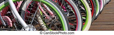 row multicolored bicycle wheels closeup