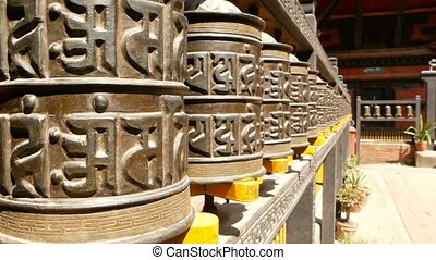 Row of aged religious prayer wheels or drums with mantra Om Mani Padme Hum in yard of temple, Durbar Square, Nepal, Kathmandu. Tibetian buddhism.