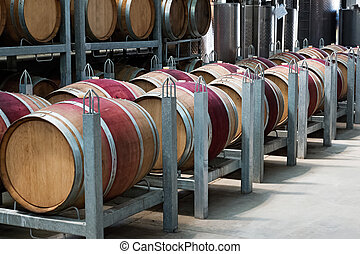 Row of barrels with red wine in a modern winery.