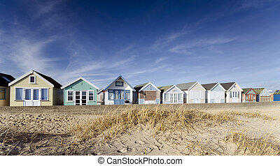 Brightly coloured row of beach huts on Mudeford Spit near Christchurch in Dorset