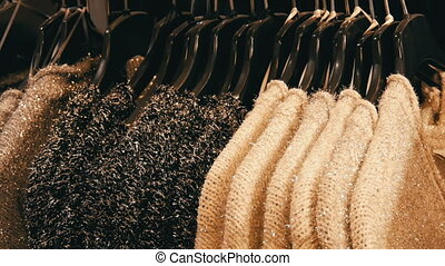 Row of beautiful warm women's fluffy sweaters of gray, black and white are hanging on black hangers in the store of the shopping center or mall. Fashionable collection of warm clothes.