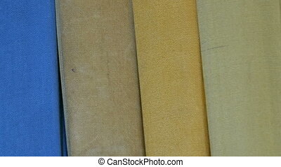 Row of big old multi-colored books on a bookshelf in...